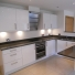 white gloss kitchen cupboards with a quartz worktop over and aeg appliances